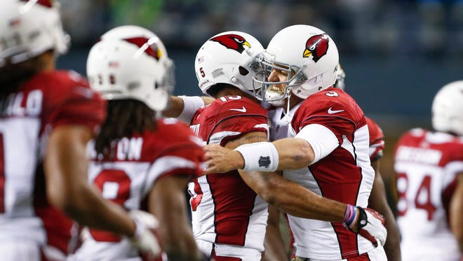 Arizona Cardinals quarterback Carson Palmer (3) hugs wide receiver Michael Floyd (15) following their touchdown pass and reception, respectively, against the Seattle Seahawks during the second quarter at CenturyLink Field.