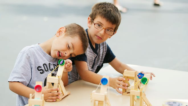 Zeynel Yucel, 4, left, and his brother, Noah, 6, test catapults on Saturday at the STEMtastic Day of Discovery event at the School District of Lee County in Fort Myers. Free interactive demonstrations related to science, technology, engineering and math were featured at the event. The Foundation for Lee County Public Schools and the Lee County School District partnered in presenting the activities.
