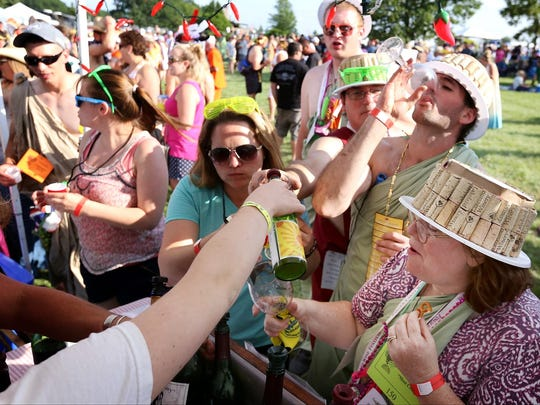 Wine enthusiasts get their cups filled at a tent at