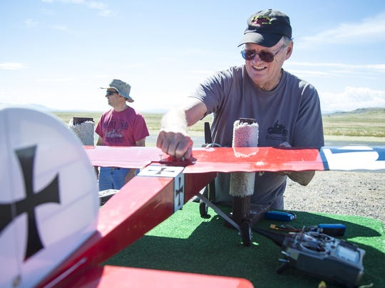 "Larry Olson tightens a plastic screw on one of his model aircraft known as an ""Ugly Stick"" during the Big Sky RC Modelers Annual Open House and Fly-In on July 17."