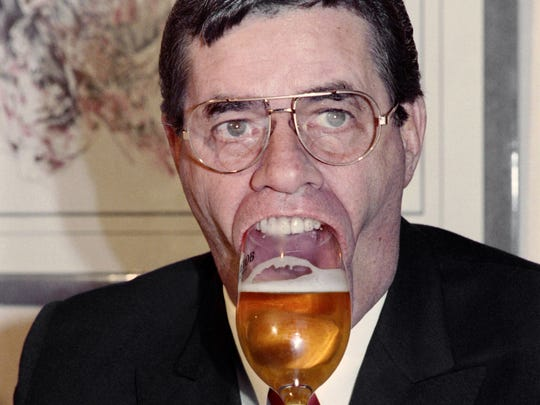"""US humorist, comedian, director and singer Jerry Lewis holds a glass of beer with his mouth, on November 27, 1987 during a press conference in Paris. Born in 1926, Jerry Lewis appeared in about fifty films in the 50s and 60s such as """"My friend Irma"""" with Dean Martin and directed different films such as """"the Nutty Professor"""". In the 70s he mainly acted in TV shows and the theater."""