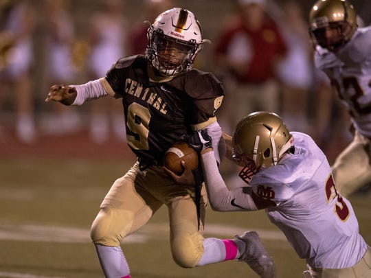 Central's Tor'Jon Evans (9) breaks a tackle by Mater Dei's Walker Massey (3) to score a touchdown at Central Stadium Friday night.