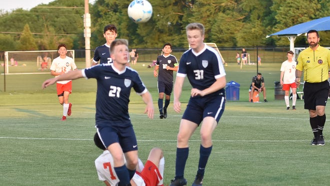 Siegel's Ryan Schofield (21) and Tristan Baker (37) go after a loose ball during Tuesday's 7-AAA semifinals. The Stars won 1-0 to earn a region berth.