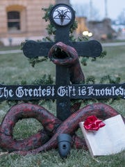 Members of the Detroit chapter of the Satanic Temple set up a Snaketivity display on the grounds of the state Capitol early morning Sunday December, 21, 2014 .
