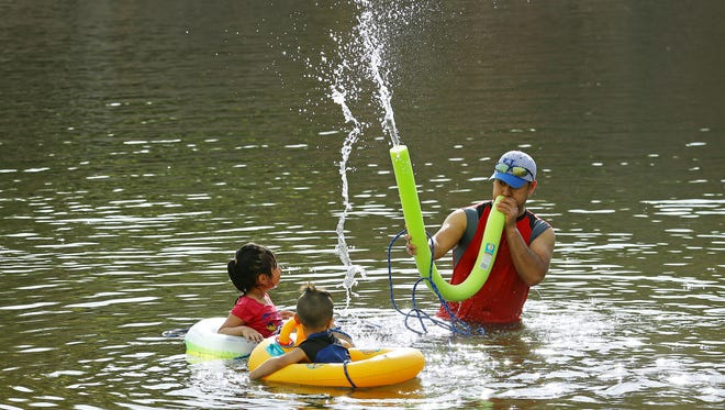 Anastacio Munoz plays with his children, Allison and Christopher, in the Salt River on April 23, 2017, in Mesa.