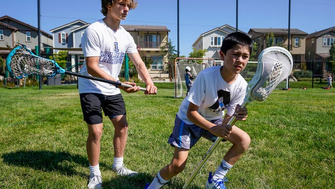 Zach Appel, right, Acalanes High School Varsity Lacrosse player, coaches 11-year-old Noah Shacklford on Tuesday, July 28, 2020 in Orinda, Calif. Zach and his friend Owen Estee have launched Lacrosse Against Hunger, to offer lacrosse coaching sessions to 7-14 year olds in exchange for a charitable donation to White Pony Express. All money raised goes directly to White Pony Express through Lacrosse Against Hunger's GoFundMe page.