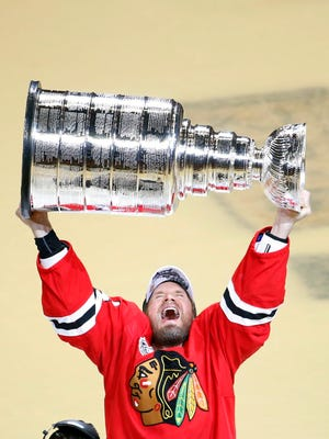 Chicago Blackhawks' Kimmo Timonen hoists the Stanley Cup trophy after defeating the Tampa Bay Lightning in Game 6 of the NHL hockey Stanley Cup Final series on Wednesday, June 10, 2015, in Chicago.
