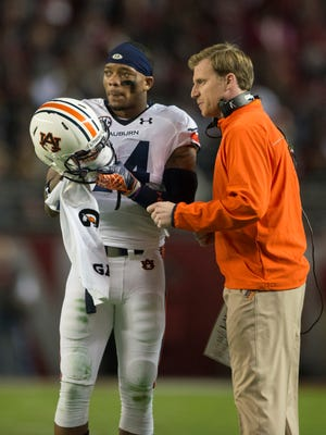 Auburn quarterback Nick Marshall talks to Tigers offensive coordinator Rhett Lashlee during the 2014 Iron Bowl. Lashlee has reportedly interviewed this week for the head coach opening at the University of Louisiana at Monroe.