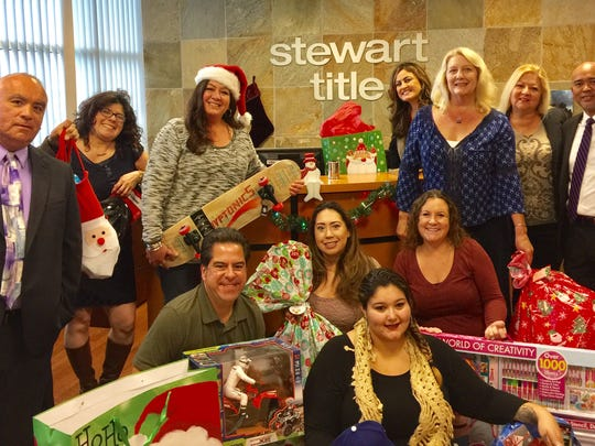 Stewart Title staff members pose with some of the items they collected to fulfill the wish lists of children at Casa Pacifica.
