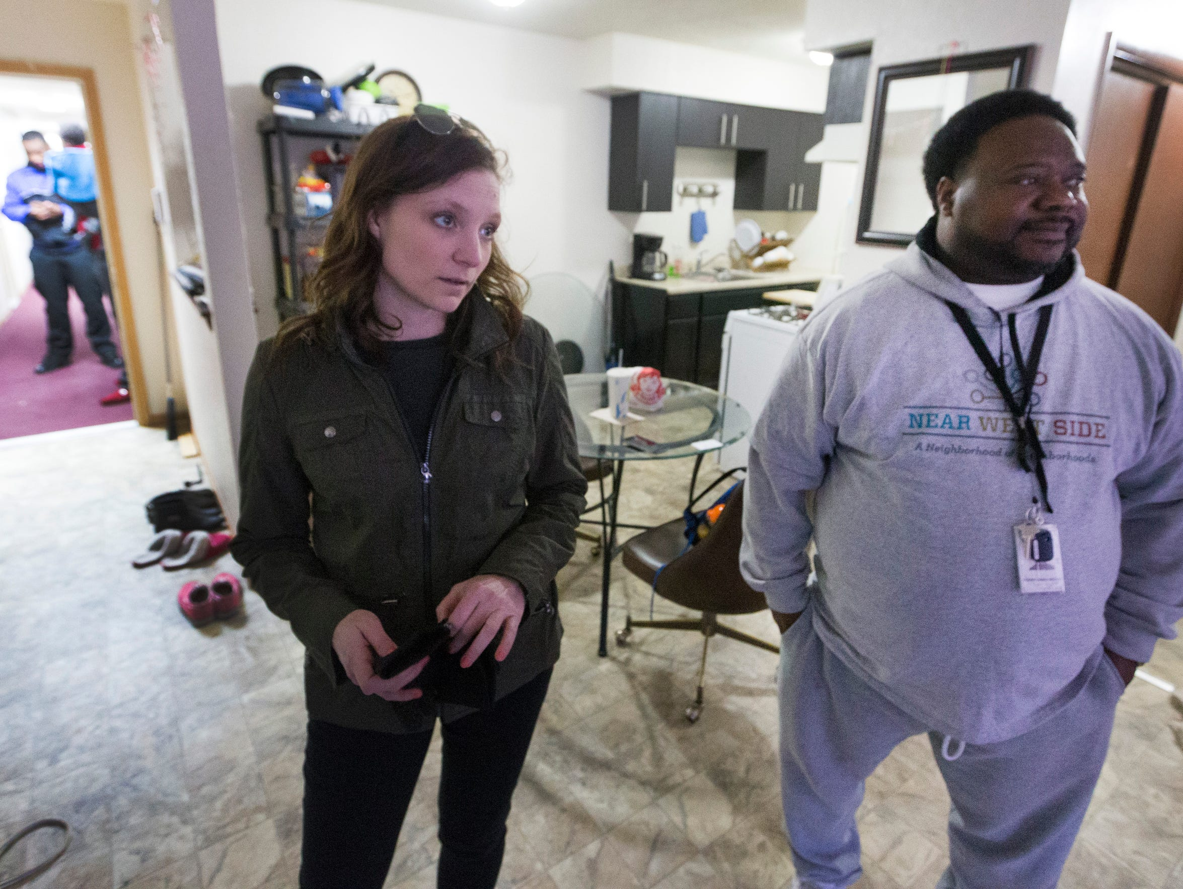 """Assistant district attorney Catelin Ringersma (left) and Safe & Sound community prosecution unit coordinator Bobby McQuay Jr. meet with a tenant who has been having problems with her rental unit during a """"blight sweep"""" March 14 on the near west side of Milwaukee."""