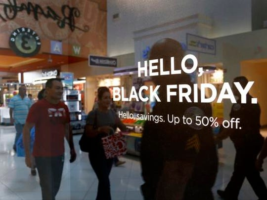 Shoppers walk by signage advertising Black Friday sales
