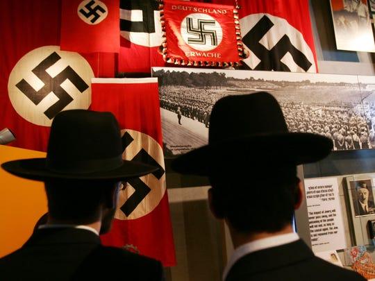 Ultra-Orthodox Jews look at an exhibit on Adolf Hitler