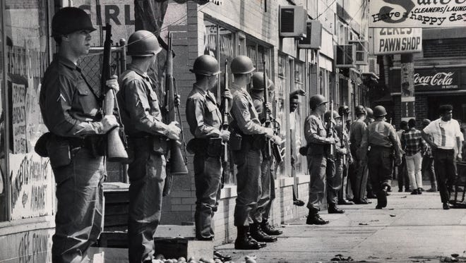 NATIONAL GUARDSMEN STAND WITH RIFLES READY IN FRONT OF LOOTED STORES ON THE EAST SIDE OF 28TH BETWEEN DUMESNIL AND VIRGINIA. ABOUT A DOZEN WEST END STORES WERE BROKEN INTO.  MAY 28, 1968