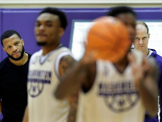 Washington head coach Mike Hopkins, right, and assistant coach Will Conroy, left, watch as guards Carlos Johnson and David Crisp take part in a drill. Hopkins gives Conroy and UW's other assistants -- Dave Rice and Cameron Dollar -- broad authority during practices and games.