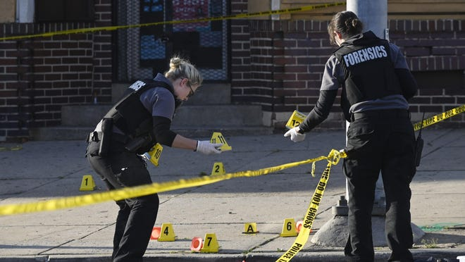 Baltimore police forensics officers place evidence markers next to bullet casings while investigating the scene of a shooting in Baltimore on Sunday, April 28, 2019. A gunman fired indiscriminately into a crowd that had gathered for Sunday afternoon cookouts along a west Baltimore street, killing one person and wounding seven others.
