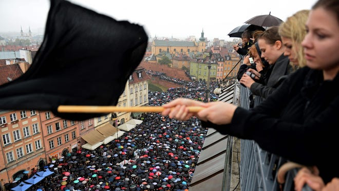 A girl waves a black flag as people take part in a nationwide strike and demonstration to protest against a legislative proposal for a total ban of abortion on October 3, 2016 in Warsaw.