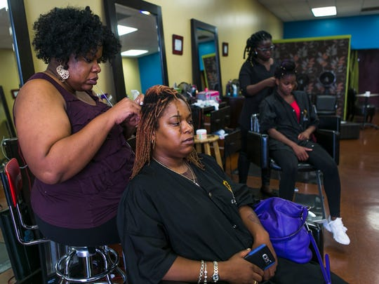 Takeisha Berry Brooks, owner of A Natural Affair Beauty Lounge in East Memphis, re-tightens Zaneta Bryant's sisterlocks during a session on Thursday. Brooks is accepting apprentices like Angelina Liom, third from left, from the Institute of Beauty, the state's first natural hair school located in Bartlett.