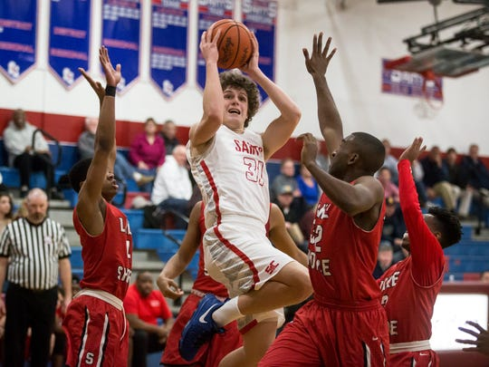 St. Clair's Ben Davidson goes for a layup surrounded by Lake Shore defenders during a basketball game Tuesday, Jan. 31, 2017 at St. Clair High School.