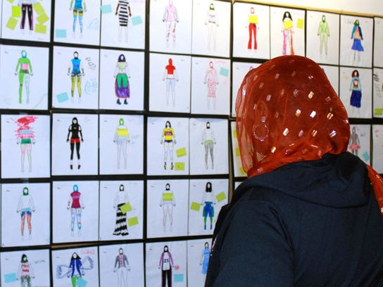 A woman looks at design drawings for Muslim girls'