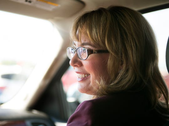 Gabby Giffords looks toward her husband, Mark Kelly, as they drive home after attending the YWCA Tucson Women's Leadership Conference in Tucson on Sept. 23, 2014.