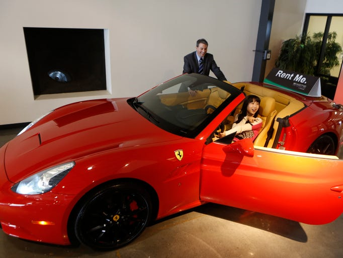 Adam Belsky, Enterprise Exotic Car Collection manager shows Jingyi Yang, 21, from Seattle a 2014 Ferrari California displayed for rent at the Enterprise Exotic Car Collection showroom near Los Angeles International Airport
