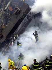 New York City firefighters work in the burning rubble as they search for victims at  Ground Zero on Sept. 12, 2001.