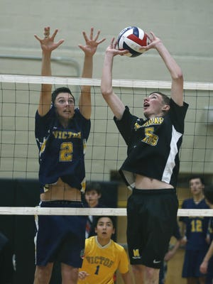 McQuaid's Christopher Mahar sets up as Victor's Paul Kopp jumps at the same time to block in the third set at McQuaid Jesuit High School.