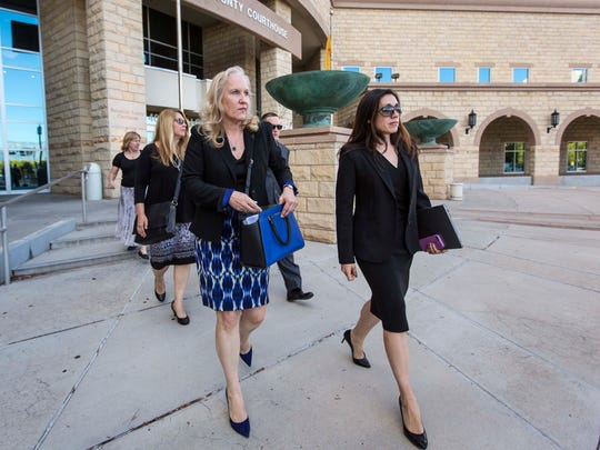 Special prosecutors Randi McGinn, left, and Elicia Montoya, right, exit the courthouse, Tuesday, Oct. 11, 2016 in Albuquerque, N.M. The case against two former New Mexico police officers charged in the death of a homeless man ended in a mistrial Tuesday when jurors told the judge they were hopelessly deadlocked on the counts of second-degree murder.