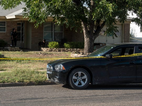 A black Dodge Charger is taped off as part of the crime