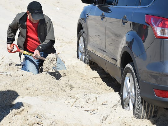 Glenn Vitale, of Lewes, digs sand from underneath his car after getting stuck during a class in How to Drive on Delaware Beaches.