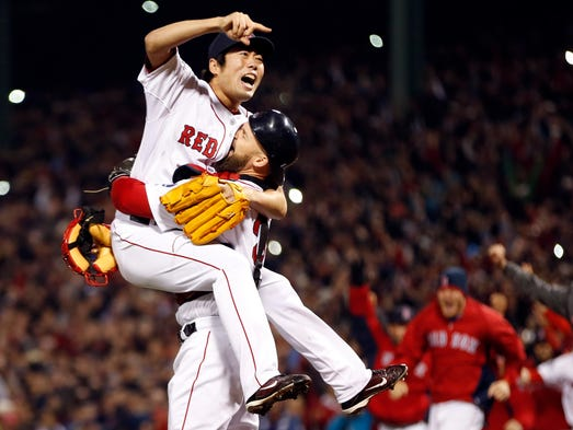 Red Sox relief pitcher Koji Uehara reacts with catcher David Ross after defeating the Cardinals at Fenway Park.