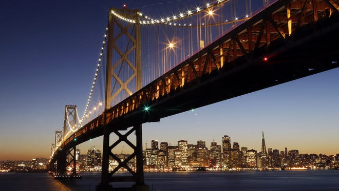The San Francisco-Oakland Bay Bridge towers over the city skyline at dusk. Shortly after 2:30 a.m., Tuesday, a quake struck 35 miles outside the city of San Francisco.