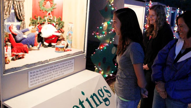 "Kirstin Bell (left), with her friend Brianna Furman and mother Leslie Bell, walk down the line of shadowboxes depicting the Christmas story ""Twas the Night Before Christmas"" on display in the Santa Rita neighborhood in San Angelo in 2013."