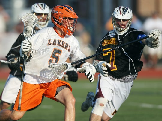 Mountain Lakes' Chet Morgis is checked by Madison's Mike Kearney  in the Group 1 boys lacrosse final at Livingston High School.  June 2, 2016, Livingston, NJ