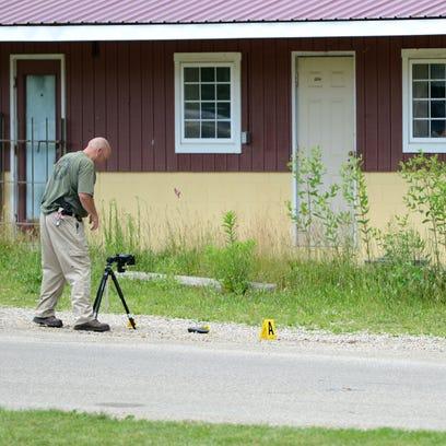 Investigators take photos at the crime scene where