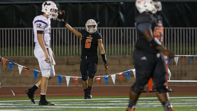 Refugio's Ysidro Mascorro holds up the ball after scoring a touchdown during the third quarter of the Class 2A Regional semifinal game against Holland at Gustafson Stadium in San Antonio on Friday, Dec. 1, 2017.