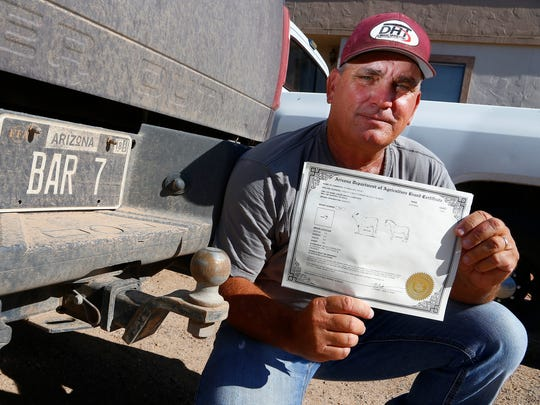 Rancher David Stambaugh holds his cattle brand certificate