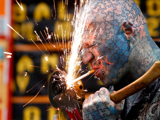 Paul Lawrence, also known as The Enigma, lights a cigarette with a hand saw at the 4th annual 2015 Louisville Tattoo Arts Convention.  May 16, 2015