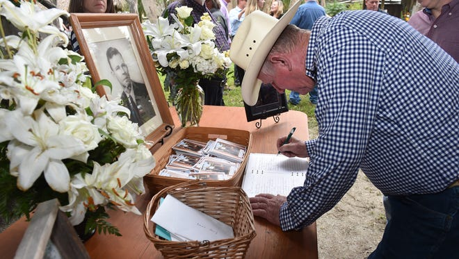 """Rip Storey, a rancher from Fort Drum, signs the registry in front of a younger portrait of Alto """"Bud"""" Adams Jr.  """"It's a sad deal for me, but it's a great honor to be able to come to know someone as great as him,"""" Storey said."""
