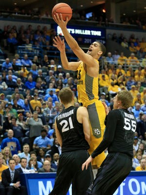 Marquette guard Haanif Cheatham, center, is fouled by Xavier forward Tim Stainbrook, left.