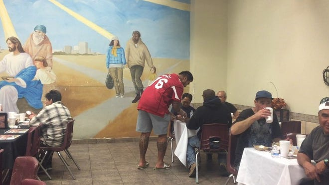 """Arizona Cardinals guard Mike Iupati serves attendees of the 14th annual """"Help feed the hungry"""" event at the Phoenix Rescue Mission on Monday, Nov. 23, 2015."""