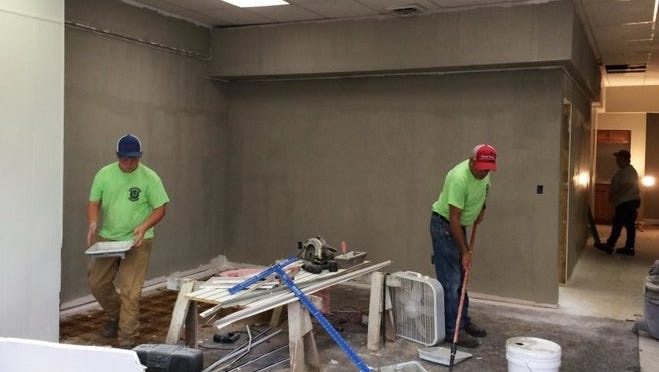 Logan Fleming (left) and Danny Adamson with Bealmear Services work to renovate the old Matt's Newsstand building before Sept. 1 when Involvement Inc. is scheduled to move in.