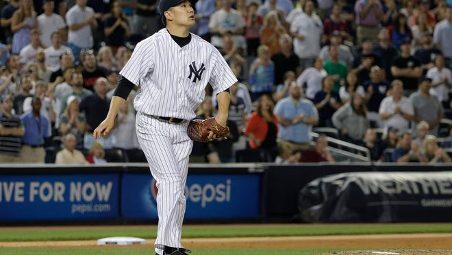 Yankees pitcher Masahiro Tanaka turns and watches a solo home run by Boston's Mike Napoli during the ninth inning that proved to be the difference in Saturday's game.