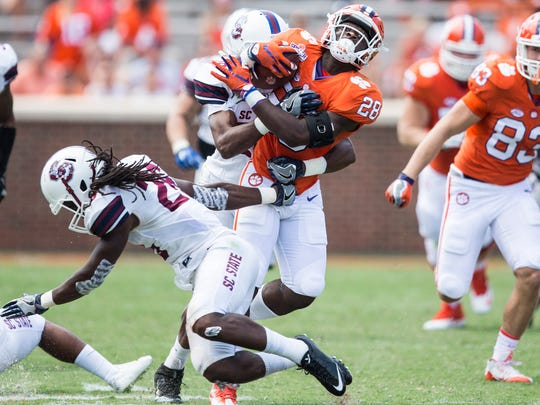 Clemson running back Tavien Feaster (28) is tackles by SC State linebacker Johnell Brown (28) during the Clemson game against South Carolina State on Saturday, September 17, 2016 in Clemson.