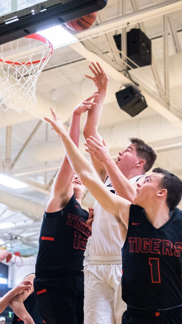 Rosman's Jonah Whitman and Hooper Thomas guard North Buncombe's Holden Ballard as he attempts to make a shot during their game in Tuscola's Holiday Classic tournament Thursday, December 28, 2017.