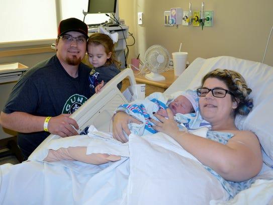 Greg Blacksill hold 2-year-old Addison while Carissa