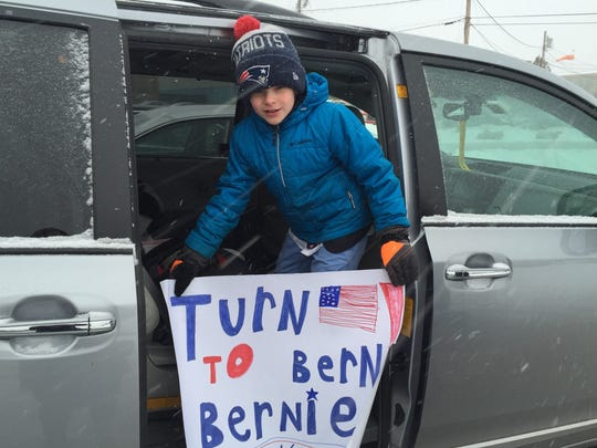 James DeFilippi, 8, of Swampscott, Massachusetts, shows off a homemade sign for Bernie Sanders after a campaign rally Monday in Nashua, N.H.
