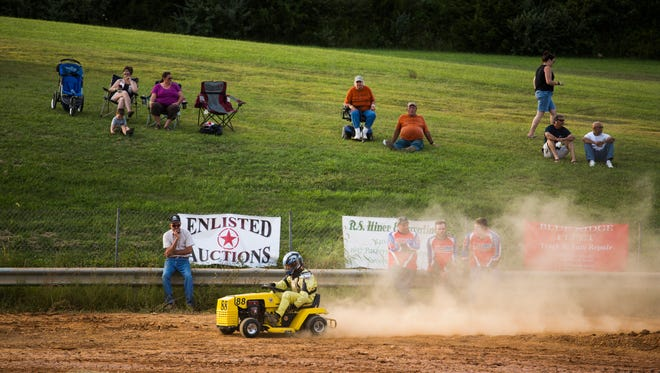 Lawn mower racers make their way around the track at the Augusta County Fair on Wednesday, August 5, 2015.