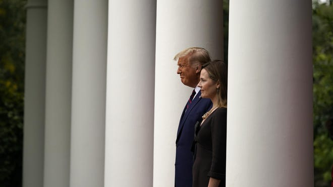 President Donald Trump walks with Judge Amy Coney Barrett to a news conference to announce Barrett as his nominee to the Supreme Court, in the Rose Garden at the White House, Saturday, in Washington.