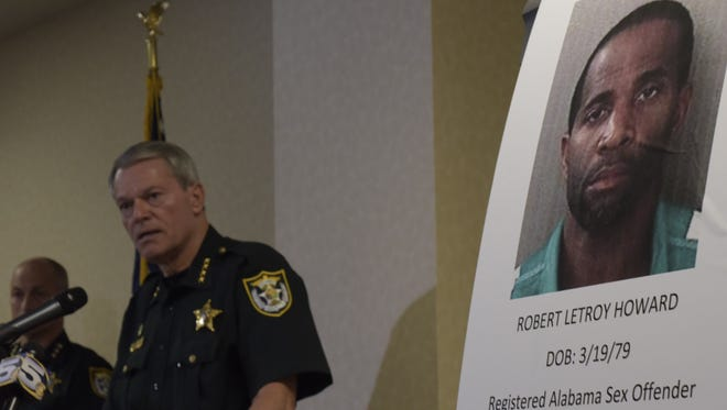Escambia County Sheriff David Morgan stands in front of a photo of Robert Letroy Howard, the suspect accused of killing 12-year-old Naomi Jones.